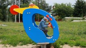 Los juegos de niños en el patio montan un helicóptero de la atracción Entretenimiento para los niños almacen de video
