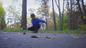 Los juegos de niños juegan el beyblade del giroscopio al aire libre en parque del otoño