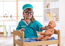 Los juegos de niños se cuidan con la muñeca en cuarto de niños fotografía de archivo libre de regalías