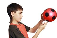 Los juegos del adolescente con una bola Foto de archivo libre de regalías