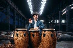 Los juegos del batería en los tambores africanos en fábrica hacen compras Fotos de archivo libres de regalías