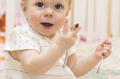 Los juegos del bebé con las cucharas. Imagen de archivo