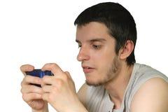 Los juegos del hombre joven en el smartphone Imagen de archivo