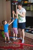 Los juegos del padre con sus hijos El padre detiene a su hijo en sus brazos foto de archivo libre de regalías
