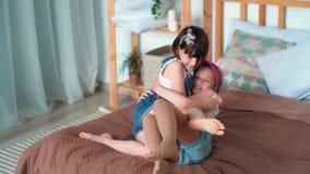 Los juegos lindos de la muchacha con las trenzas, se sientan en cama, su hermana saltan en ella, cámara lenta metrajes
