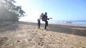 Los juegos rubios del guitarrista en muchacha rubia de la playa ligan en el amanecer metrajes