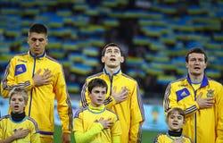 Los jugadores de equipo de fútbol nacionales de Ucrania escuchan el anthe nacional Imagenes de archivo