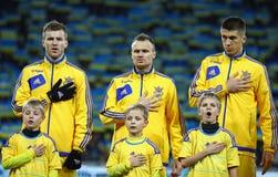 Los jugadores de equipo de fútbol nacionales de Ucrania escuchan el anthe nacional Imagen de archivo