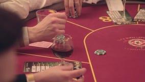 Los jugadores de póker en la tabla hacen apuestas En el marco solamente la tabla y las manos almacen de video