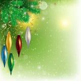 Los juguetes coloreados colgantes en la ramita con el vuelo nievan en backg verde Foto de archivo libre de regalías