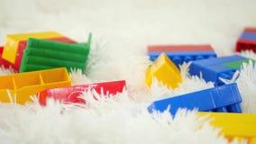 Los juguetes de los bloques del color mienten en un primer blanco del fondo Movimiento del resbalador de la cámara metrajes