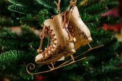 Los juguetes de la Navidad en los patines de oro de la forma cuelgan en una rama spruce Fotografía de archivo