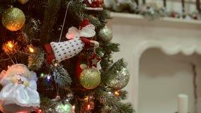 Los juguetes de la Navidad y del Año Nuevo en el árbol de navidad entre el centelleo se encienden almacen de metraje de vídeo