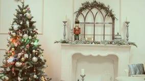 Los juguetes de la Navidad y del Año Nuevo en el árbol de navidad entre el centelleo se encienden metrajes