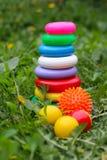 Los juguetes de los niños en la hierba Fotos de archivo libres de regalías