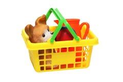 Los juguetes de los niños plásticos en una cesta Foto de archivo