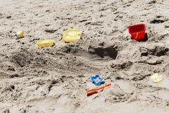 Los juguetes de los niños que mienten en la arena Fotografía de archivo libre de regalías