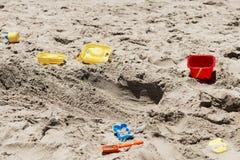 Los juguetes de los niños que mienten en la arena Imagen de archivo