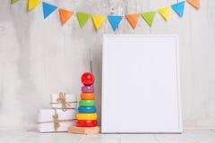 Los juguetes de los niños, con un marco blanco el marco en un fondo ligero de la pared con las muestras de los niños, para el dis imagen de archivo