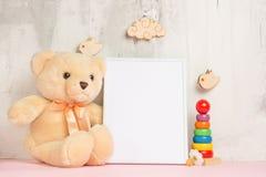 Los juguetes de los niños, un oso de peluche y un marco en un fondo ligero de la pared, para el diseño, disposición Ducha de bebé foto de archivo