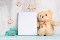 Los juguetes de los niños, un oso de peluche y un marco en un fondo ligero de la pared, para el diseño, disposición Ducha de bebé imagen de archivo