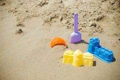 Los juguetes de los ni?os pl?sticos brillantes en la arena Concepto de reconstrucci?n de la playa para los ni?os Juegos del veran fotos de archivo libres de regalías