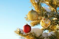 Los juguetes del Año Nuevo cuelgan en un árbol de pino nevado Fotografía de archivo libre de regalías
