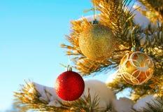 Los juguetes del Año Nuevo cuelgan en un árbol nevado Imagen de archivo