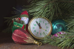 Los juguetes del Año Nuevo desde hora debajo del árbol de abeto verde en backgrou oscuro Imagen de archivo libre de regalías