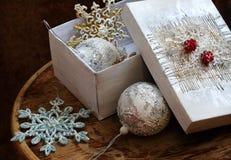 Los juguetes del Año Nuevo en una caja blanca en una tabla de madera Fotos de archivo libres de regalías
