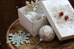 Los juguetes del Año Nuevo en una caja blanca en una tabla de madera Fotografía de archivo