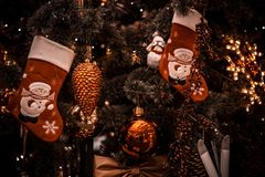 Los juguetes del ` s del Año Nuevo cuelgan en el árbol de navidad, decoración festiva en el árbol del calcetín de Santa Claus Fotografía de archivo