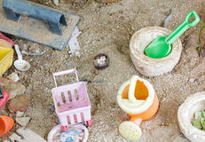 Los juguetes viejos en el fondo de la arena Fotos de archivo