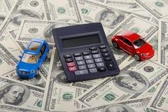 Los juguetes y la calculadora del coche permanecen en los dólares Imagenes de archivo