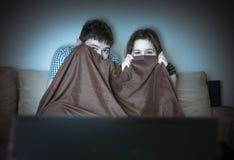 Los jóvenes asustados se juntan están mirando horror en la TV El par está cubriendo con la manta Fotografía de archivo libre de regalías