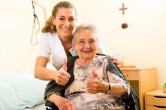 Los jóvenes cuidan y mayor femenino en clínica de reposo Foto de archivo libre de regalías