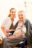 Los jóvenes cuidan y mayor femenino en clínica de reposo Imagen de archivo