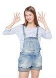 Los jóvenes felices forman a la muchacha en guardapolvos de los vaqueros que gesticula el isolat aceptable Foto de archivo
