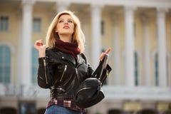 Los jóvenes forman a la mujer rubia en la chaqueta de cuero con el bolso Imagen de archivo libre de regalías