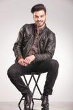 Los jóvenes sonrientes forman al hombre que se sienta en una silla Imagenes de archivo