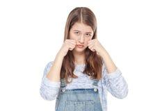 Los jóvenes tristes forman a la muchacha en los guardapolvos de los vaqueros aislados Imagen de archivo libre de regalías