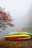 Los kajaks almacenan en muelle en el lago de niebla Muchacha que goza del bosque hermoso del otoño en mañana de niebla Fotos de archivo