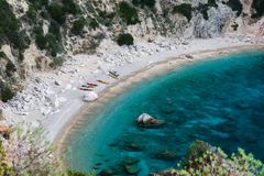 Los kajaks coloreados se colocan en la orilla arenosa en una bahía con agua azul fotos de archivo libres de regalías
