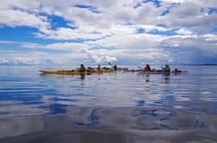Los Kayakers se baten en el océano con las nubes dramáticas reflejadas en el agua imagen de archivo libre de regalías