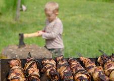 Los kebabs que asan a la parrilla en un Bbq como pequeño muchacho tajan la madera Imagenes de archivo
