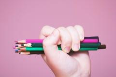 Los lápices agrupan en una mano fotos de archivo