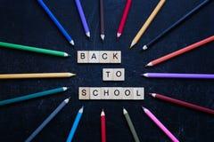 Los lápices coloreados alrededor de palabras de madera de nuevo a escuela en pizarra ennegrecen el fondo De nuevo a concepto de l Foto de archivo libre de regalías