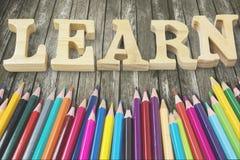 Los lápices coloreados con aprenden palabra en la tabla imagen de archivo libre de regalías