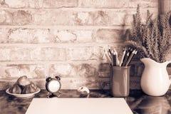 Los lápices coloreados en una taza, florero de lavanda florecen, registran, lámpara de pie, luz de la noche, placa de tortas, taz Fotografía de archivo