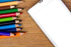 Los lápices colorean y teléfono elegante en el fondo de madera Foto de archivo libre de regalías